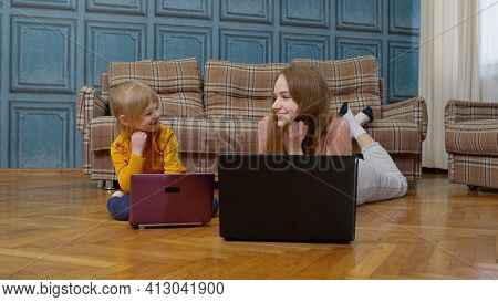 Woman Nanny And Child Girl Studying Together With Computer Laptop, While Lying On Warm Floor At Home