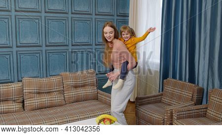 Happy Family Mother And Child Kid Daughter Dancing, Playing Piggyback, Running, Riding At Home