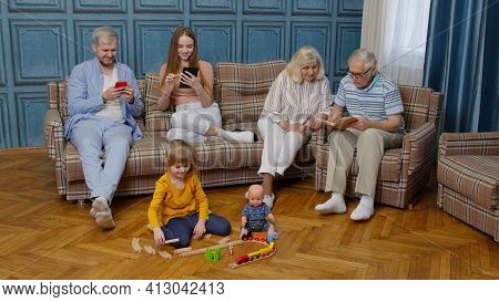 Multigenerational Family Leisure At Home Talking, Reading Book, Use Mobile Phone, Play Game On Sofa