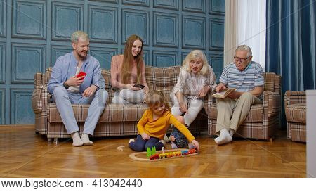 Happy Multigenerational Family Leisure At Home Couple Parents And Grandpagents Relaxing On Sofa