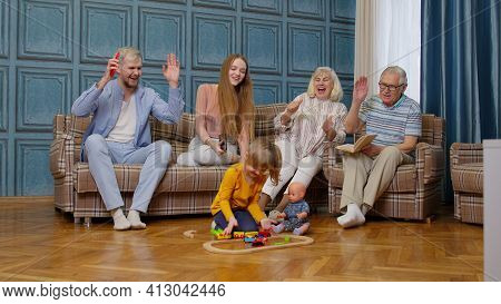 Multigenerational Family Leisure At Home, Motivating Shouting To Child Kid Girl Playing Railway Toy