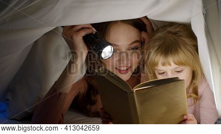 Young Mother Reading Goodnight Story Fairytale To Child Daughter Under Duvet Blanket In Night Room