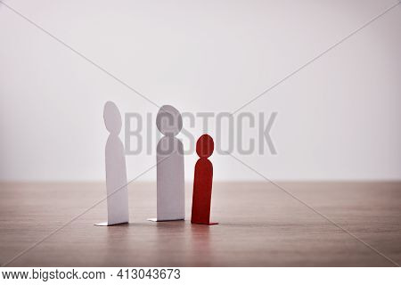 Child Bullying Concept With Cutouts Of Little Paper Men On Wooden Table And Light Background