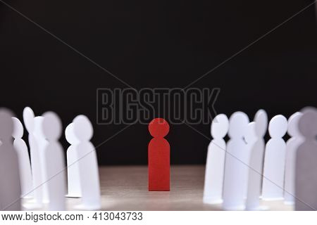 Social Discrimination Concept With Many Little White Paper Men Around A Different One On Wooden Base