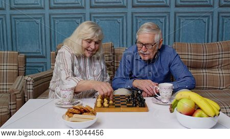Retired Senior Couple Talking Drinking Tea, Playing Chess In Modern Living Home Room Lounge Together