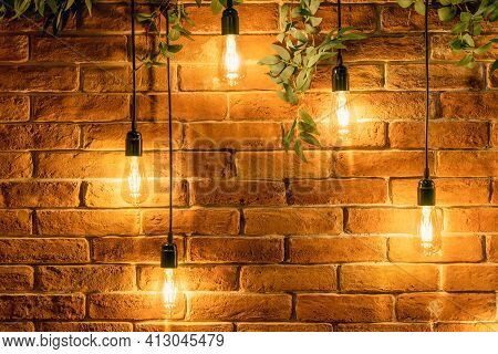 Decorative Incandescent Bulbs In Edison Style On A Brick Wall Background.