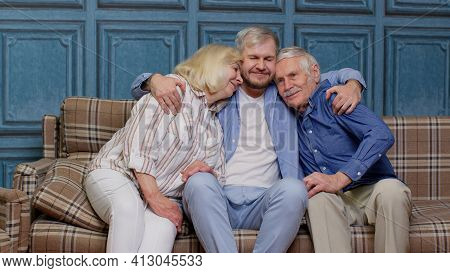 Family Of Senior Grandparents With Adult Son Embracing Having Fun Looking At Camera Bonding At Home