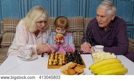 Senior Couple Grandfather, Grandmother Resting On Sofa, Playing Chess With Granddaughter Child Kid