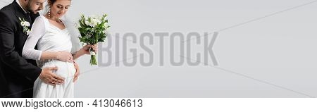 Muslim Groom Embracing Tummy Of Pregnant Bride Isolated On Grey, Banner.