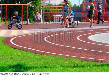 Tiraspol, Transnistria, Moldova - September 6, 2020: public stadium for sports - running track and horizontal bars, people doing physical exercises