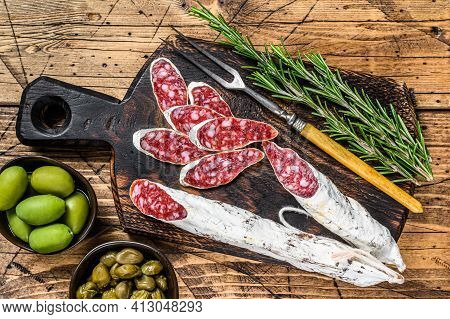 Spanish Tapas Fuet Salami Sausage Slices With Olives And Rosemary On A Wooden Board. Wooden Backgrou