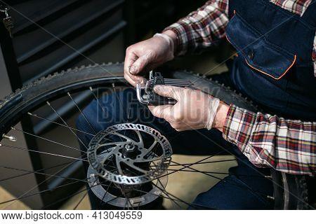 Male Mechanic Working In Bicycle Repair Shop, Mechanic Repairing Bike Using Special Tool, Wearing Pr