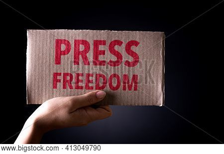 World Press Freedom Day Concept. Hand  Holding Cardboard Paper With The Text On Dark Background, Con