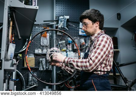 Technical Expertise Taking Care Bicycle Shop. Handsome Young Mechanic Fixing Cycle Wheel In Workshop
