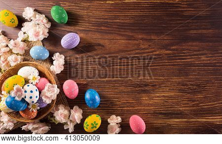 Happy Easter! Colourful Of Easter Eggs In The Nest With Flower On Dark Wooden Background. Greetings