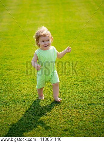 Portrait Of Cute Little Caucasian Baby Child Having Fun In Garden. Little Kid Crawling On Green Gras