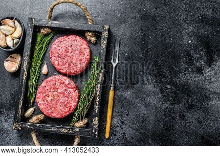 Raw Beef Meat Patties For Burger From Ground Meat And Herbs On A Wooden Board. Black Background. Top