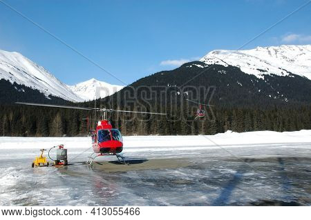 GIRDWOOD, ALASKA - 5 MAR 2007: Two Helicopters at Gridwood, Aaska Airport, one landed and one in flight