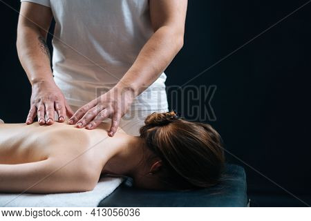Close-up Side View Of Male Masseur Massaging Back Of Young Woman Lying On Massage Table In Black Bac