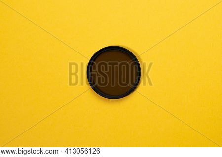 Polarizing Filter For The Camera On A Yellow Background. Photo Accessory
