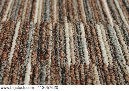 Texture Of Carpet Floor Close-up. Brown Carpet With A Pattern. Geometric Shapes On The Carpet.