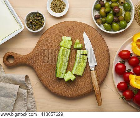Vegetarian Food. Chopping Cucumber, Cutting Vegetables For Greek Salad Horiatiki. Kitchen Knife On W