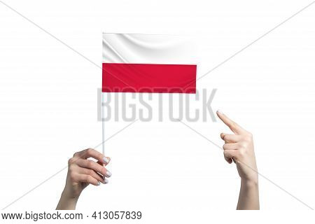 A Beautiful Female Hand Holds A Poland Flag To Which She Shows The Finger Of Her Other Hand, Isolate