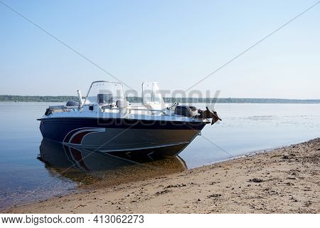 A Motorboat Stands On The Sandy Bank Of The River Without People. High Quality Photo
