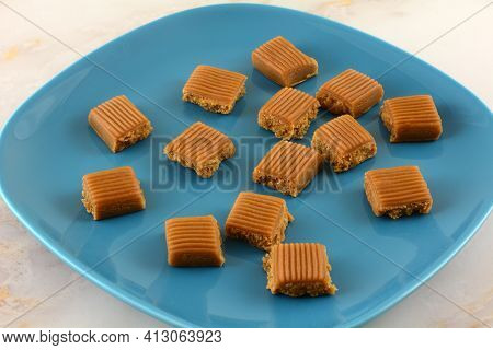 Creamy Toffee Candy Pieces Broke Off Candy Bar On Blue Dessert Plate