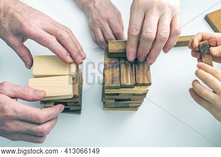 Hands Grandmother, Grandfather And Grandson Play Board Game With Wooden Blocks. Concept Of Family Re