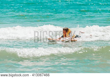 Little Kid Girl Learning Surf In Sea. Little Kid Surfer With Surfer Board On Sea Beach On Family Vac