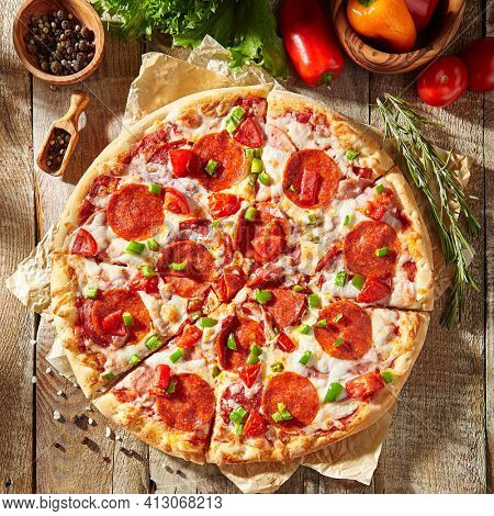 Pepperoni pizza with pizza sauce, mozzarella cheese and pepperoni. Pizza on wooden board on wood table with ingredients