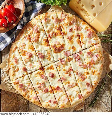 Cheese and Bacon Pizza - homemade pizza dough topped with bacon, cheese and herbs. Italian pizza on baking paper with tomato and cheese on wooden table. Fast food pizza dinner top view