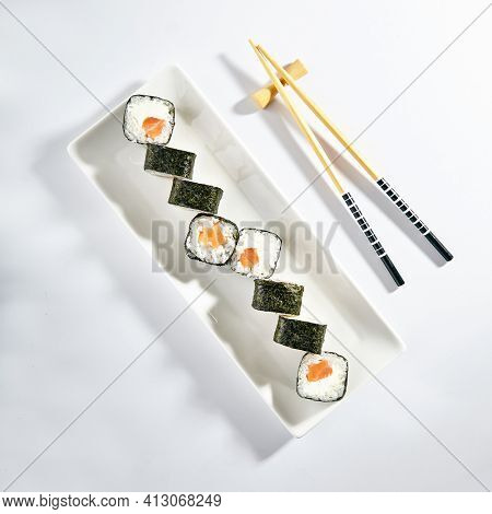 Philadelphia Sushi Roll made with Smoked Salmon. Maki sushi with nori seaweed outside, salmon and cream cheese inside. White plate with wooden chopsticks on white table. Top view