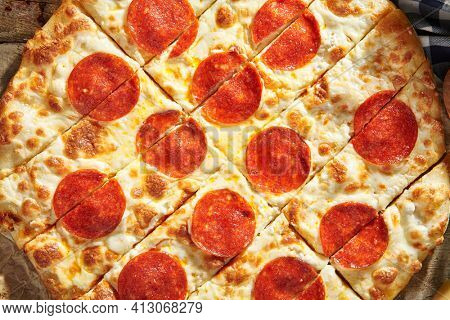 Pepperoni or Salami Pizza - homemade pizza dough topped with salami sausage slice and cheese. Italian pizza on baking paper with tomato and cheese on wooden table. Fast food dinner top view