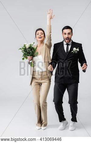 Excited Bride Demonstrating Wedding Ring Near Groom Showing Yes Gesture On Grey.