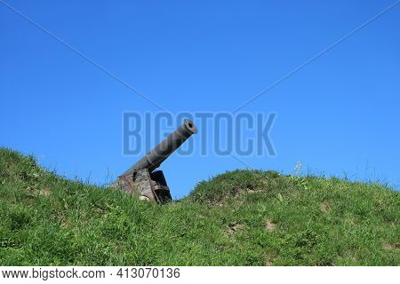 Old Cannon Painted In Black Install On Wooden Base On Green Grass Slope Hill On The Background Of Cl