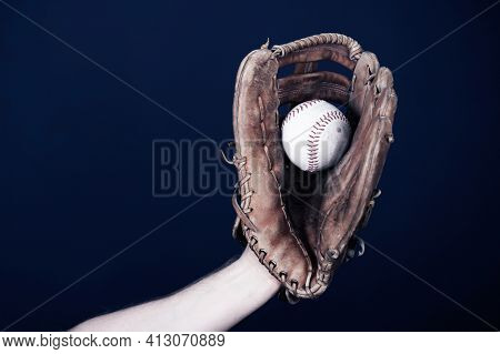 Close up image of an old used baseball and baseball glove.