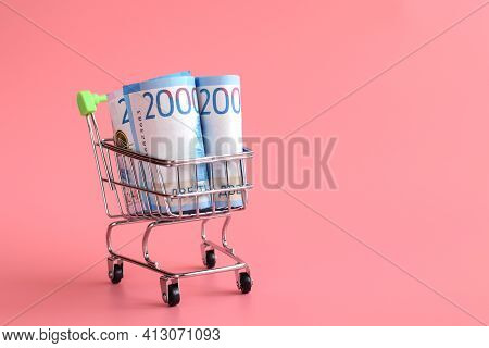 Russian Bills Of 2000 Rubles Rolled Up In A Tube In A Grocery Basket Isolated On A Pink Background.