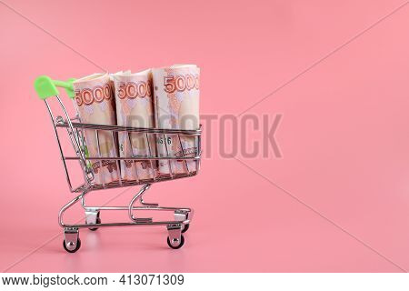 Russian Bills Of 5000 Rubles Rolled Up In A Tube In A Grocery Basket Isolated On A Pink Background.