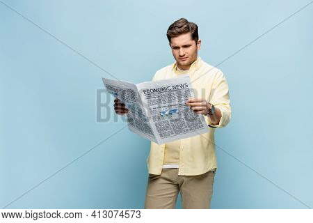 Displeased Young Man In Shirt Reading Economical Newspaper On Blue.