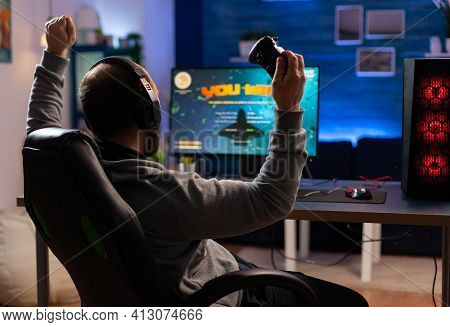 Winner Gamer Sitting On Gaming Chair At Desk And Playing Space Shooter Video Games With Controller.