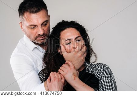 An Aggressive Man Covers The Mouth Of A Beaten Woman So That She Cannot Scream. Domestic Violence