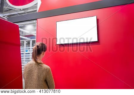 Woman Looking At Blank Digital Interactive White Display On Red Wall At Exhibition Or Museum With Fu