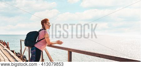 Banner. A Happy Adult Woman In Sportswear With A Backpack Posing On A Pier. In The Background, The S