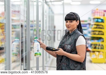 A Young Smiling Caucasian Woman Who Works As A Manager In A Supermarket Checks The Expiration Date O