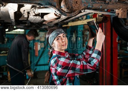 Portrait Of A Young Beautiful Female Mechanic In Uniform Who Conducts A Car Inspection Using A Diagn