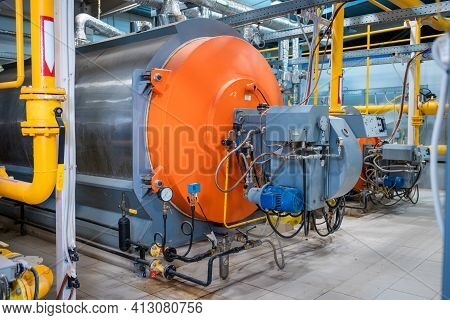 Industrial Heating Pipes And A Large Boiler. Red Vents On The Pipes. The Concept Of Industrializatio