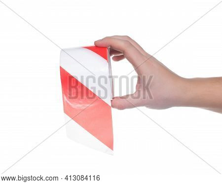 Man Holds In His Hand A Protective Signal Tape With Red Stripes On A White Background, Isolate. Clos