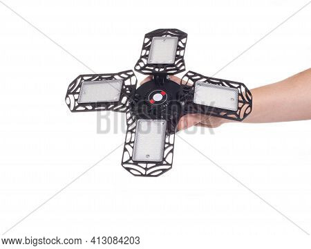 Man Holds In Hand An Illuminating Garage Spotlight On A White Background, Isolate. Close-up, Electri